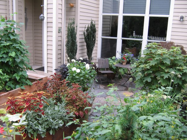 Raised garden beds surround a flagstone patio
